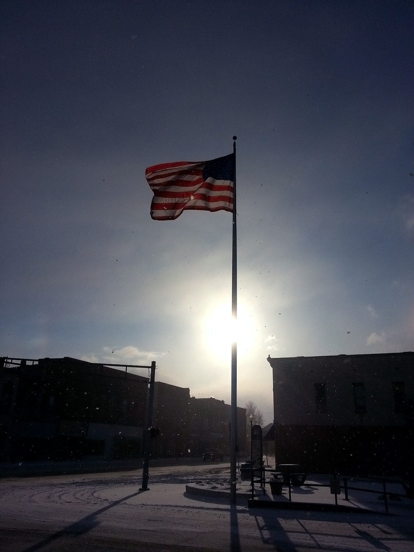 The deep cold of winter creates crisp, clear conditions on Knightstown's Public Square, located just of U.S. 40. A late afternoon sun illuminates snow flurries and Old Glory, whipping angrily in a brisk, southwesterly wind.