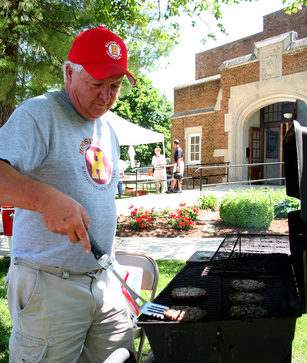 Grilling hamburgers for the concession stand in 2009, longtime Hoosier Gym volunteer Larry Loveall is no stranger to gym events. Concession stand sales bolster the gym's limited finances. That means Loveall and other gym volunteers regularly busy themselves preparing and selling hot dogs, popcorn and other items to hungry visitors.