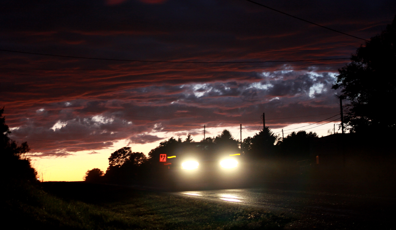 Sometimes a thoughtfully angled photograph can bring two sources of interesting light into one frame, creating an interesting photo from mundane subjects. An eastbound car on U.S. 40 speeds past the lens, while, behind it, a setting sun evokes striking colors on interesting clouds.