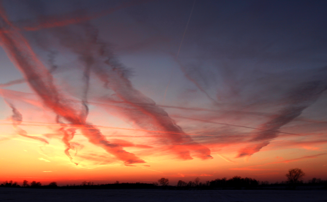 Deep cold isn't good for much, but a combination of freezing temperatures and low humidity create crystalline skies. In such conditions, inhospitable though they may be, jet contrails sometimes look surreal, here painting up a sunset like a wild-eyed watercolorist.