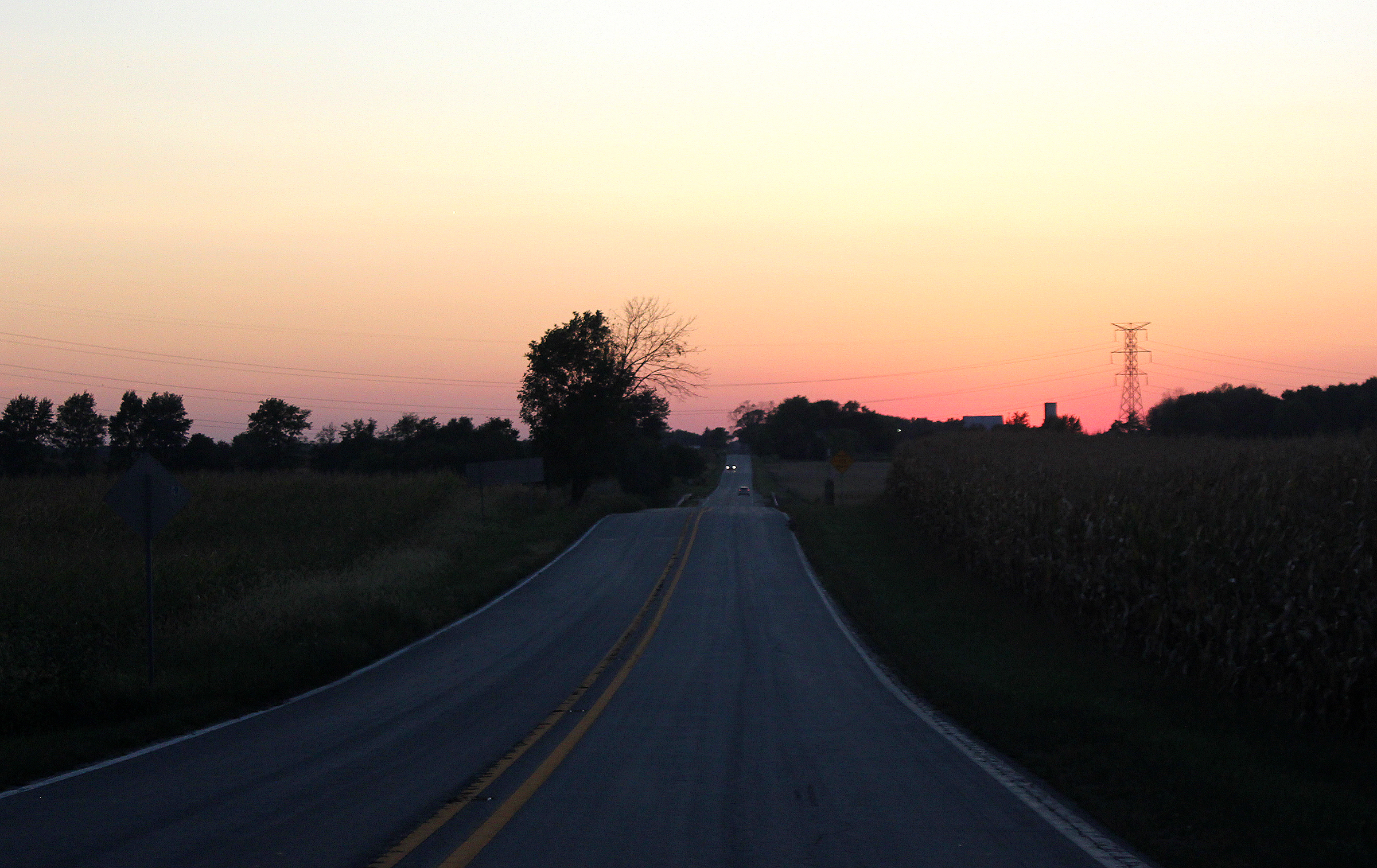 Corn on the right, beans on the left. Roads like this are obligatory travel corridors in this state. Yet, we regard them as things of beauty, particularly on nights with cloudless sunsets.
