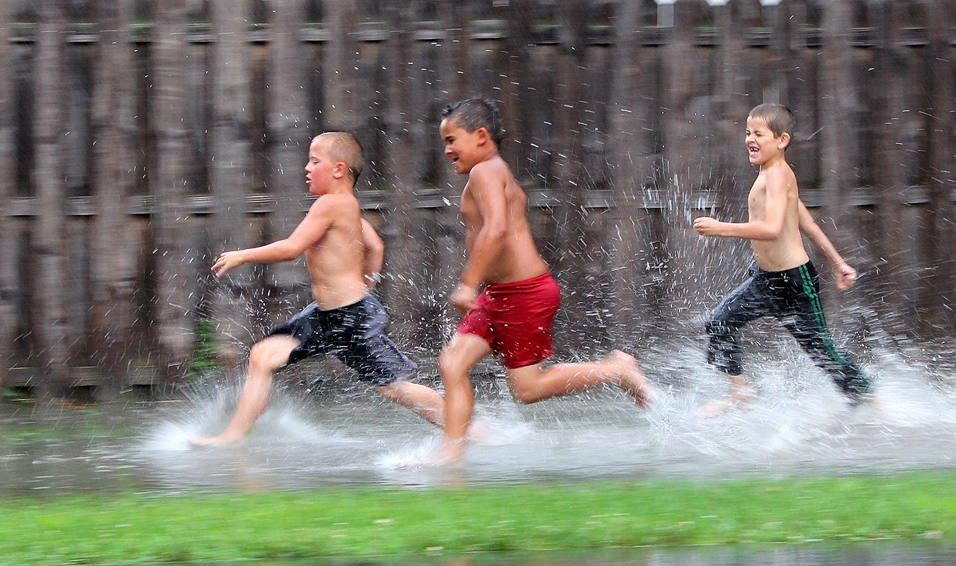 """A deluge of spring rain left pools of water in neighborhoods, where eager kids race and splash for fun. As a community newspaper publisher, a big part of my job involves photographing children doing their various activities. This always delights our readers, and the kids, well, they become instant """"celebrities"""" for the week."""