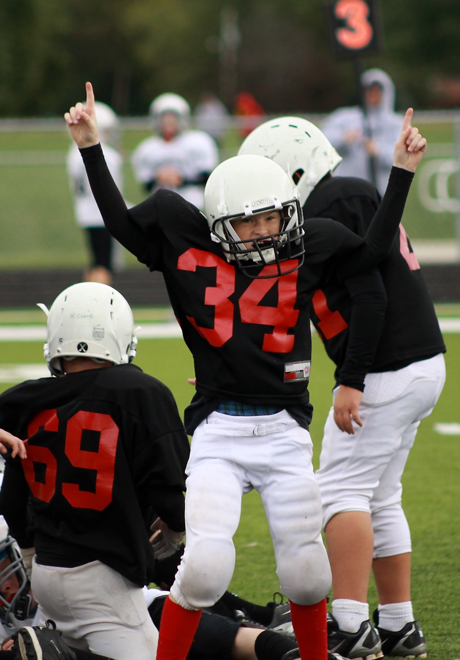 Triumph and heartbreak are consistent themes in any sport. But, the feelings concentrated when kids are playing. In this photo, a young football player reacts to his own good effort, and he looks to his parents in the stands for validation.