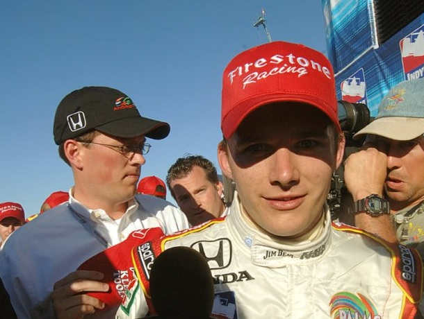 Rob Cleveland in the background as the late Dan Wheldon talks to reporters. Photo by Tom Savage